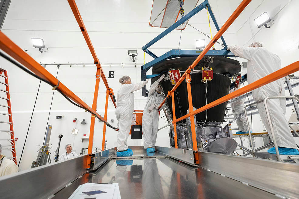Parker Solar Probe's heat shield, called the Thermal Protection System, is lifted and realigned with the spacecraft's truss as engineers from the Johns Hopkins Applied Physics Lab prepare to install the eight-foot-diameter heat shield on June 27, 2018.