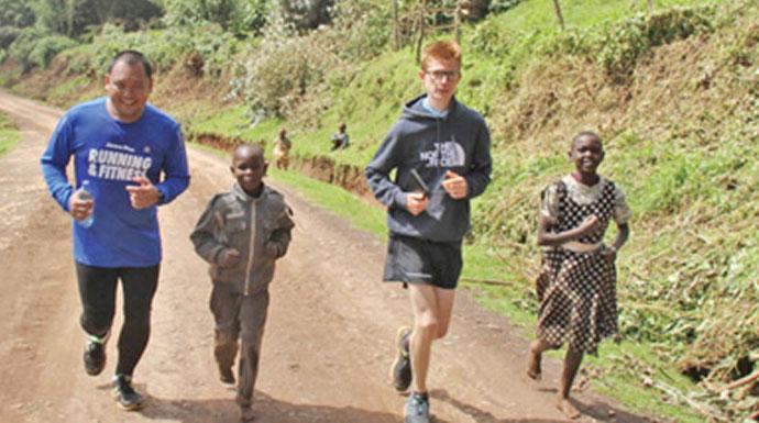 SEMANGAT: Wartawan Jawa Pos Tomy C. Gutomo dan Stefan Zak bersama anak-anak Kenya berlari di Fluorspar Hill.
