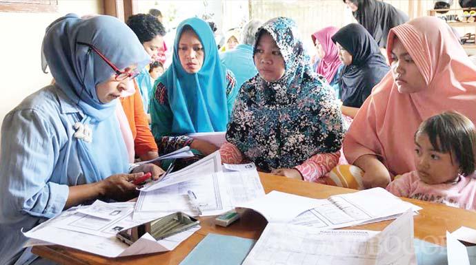 LAYANI: Petugas Disdukcapil saat melayani masyarakat Kelurahan Katulampa membuat akta, kemarin (23/10).