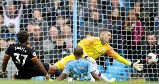 Pemain sayap Wolverhampton Adama Traore (kiri) mencetak gol ke gawang Manchester City disaksikan kiper Ederson Moraes (atas) dan bek Fernandinho (kanan) dalam laga lanjutan Liga Inggris di Stadion Etihad, Manchester, Inggris, Minggu (6/10/2019).