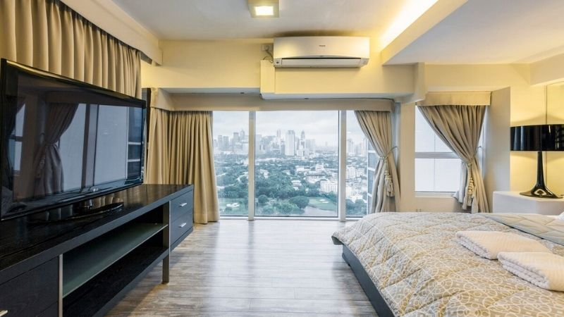 bedroom in bgc airbnb with floor to ceiling windows